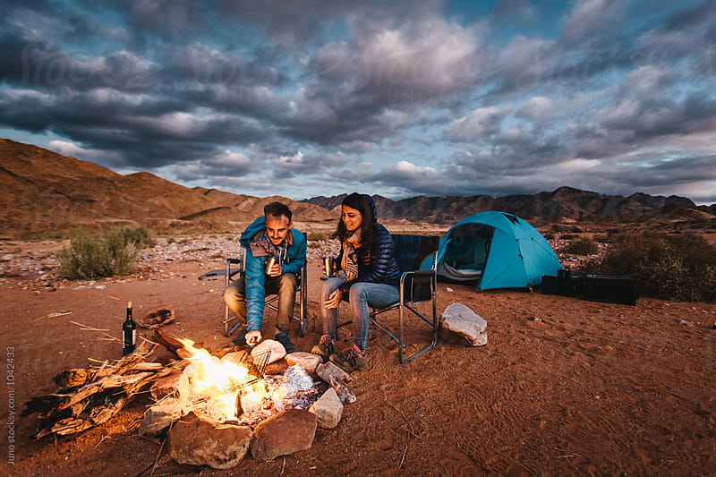 Hikers at their camp fire at dusk by Micky Wiswedel for Stocksy United