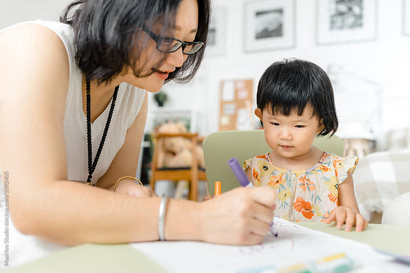 Adorable little girl drawing pictures with her mother by MaaHoo Studio for Stocksy United