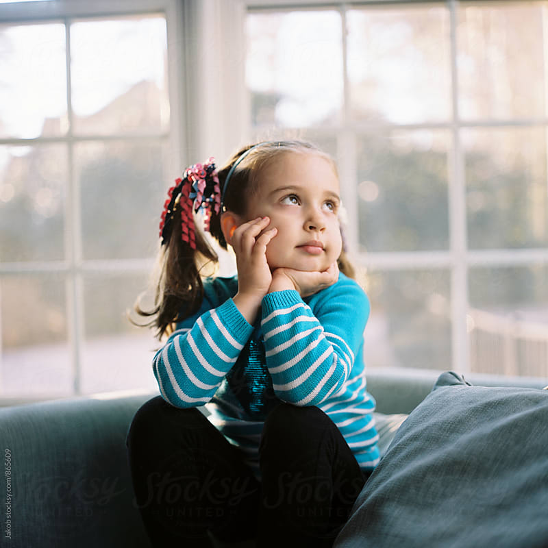 Cute young girl sitting in a chair looking bored by Jakob for Stocksy United