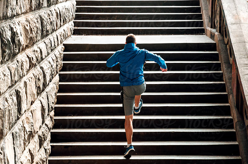 Young  man running up the stairs by Dimitrije Tanaskovic for Stocksy United
