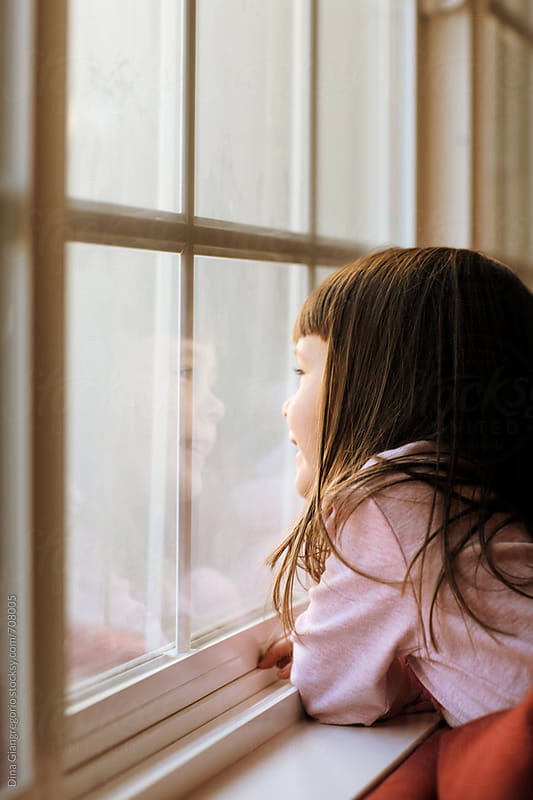 Little Girl With Long Hair Looking Out Window by Dina Giangregorio for Stocksy United