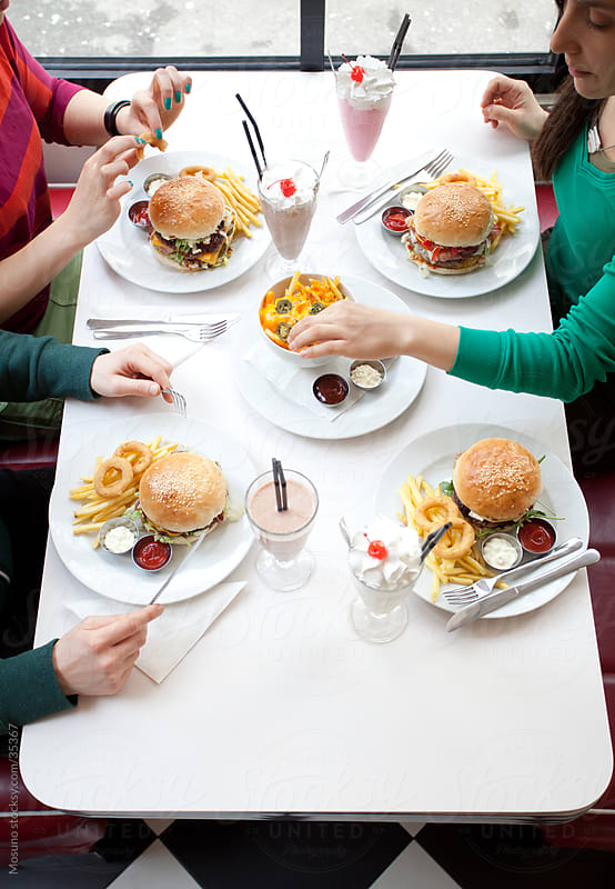 People eating fast food served in a restaurant.  by Mosuno for Stocksy United