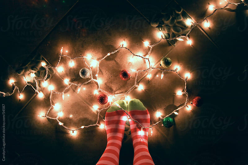 Green and Red striped knee high socks and party lights  by Carolyn Lagattuta for Stocksy United