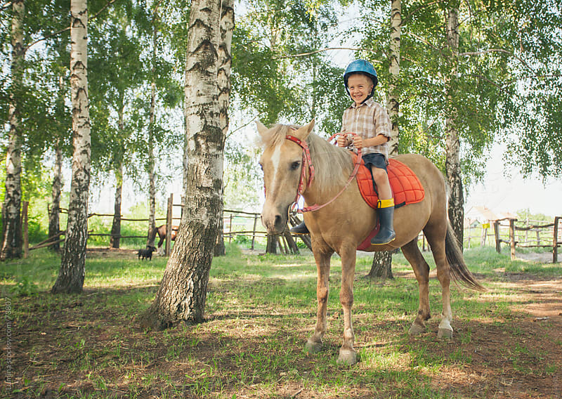 Smiling Boy Riding a Horse by Lumina for Stocksy United