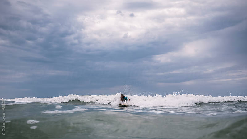 Surfer riding the waves by GIC for Stocksy United