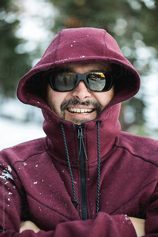 Man wearing a zipped up jacket and sunglasses smiling in the snow by Amy Covington for Stocksy United