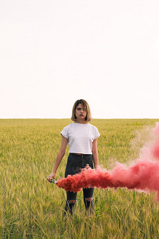 Teen girl with bright smoke bomb on field by Danil Nevsky for Stocksy United
