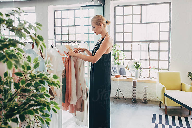 Woman Choosing Clothes by Lumina for Stocksy United