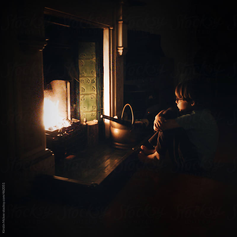 Boy sitting by a cosy fire by Kirstin Mckee for Stocksy United