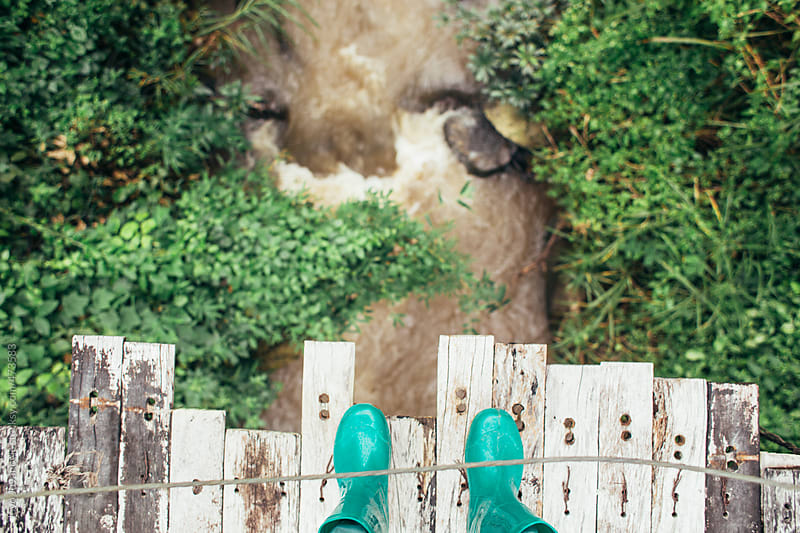 Looking over the edge of wooden bridge in green gum boots  by Jovo Jovanovic for Stocksy United