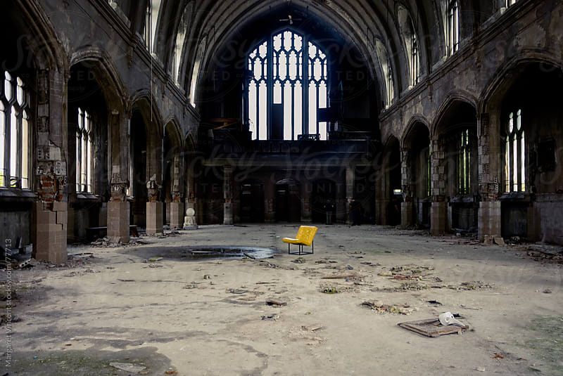 yellow chair sits alone in an empty, decaying church by Margaret Vincent for Stocksy United