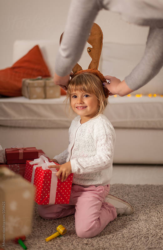 Little Girl Opening Christmas Gift at Home by Mosuno for Stocksy United