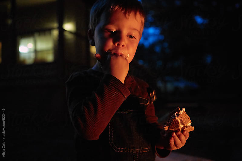 Young boy eating s'more by Alicja Colon for Stocksy United