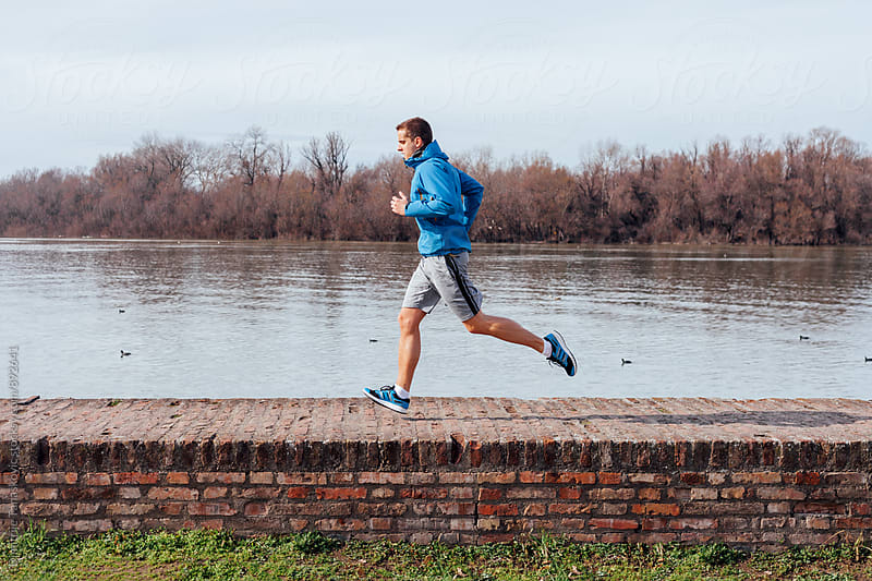Man running by the river by Dimitrije Tanaskovic for Stocksy United