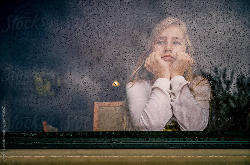 Girl looking out a window on a rainy day by Angela Lumsden for Stocksy United