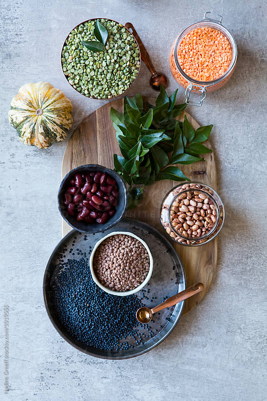 Cooking ingredients, dried beans, lentils, squash, pulses, legumes and fresh curry leaves by Nadine Greeff for Stocksy United