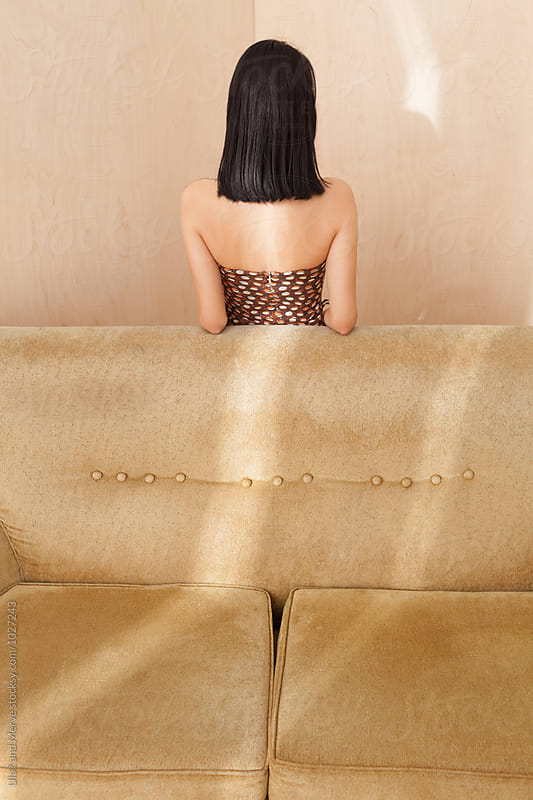 young woman posing behind a retro couch by Ulaş and Merve for Stocksy United