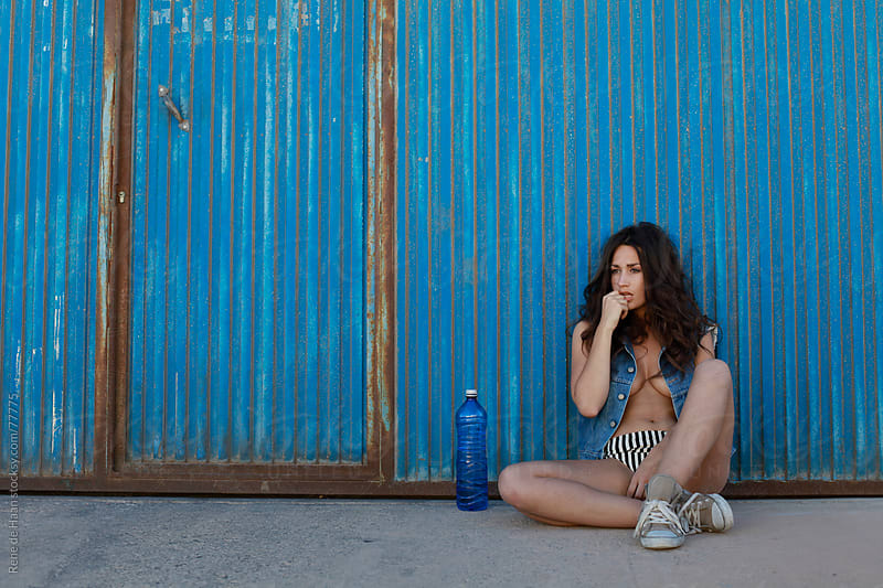 girl with waterbottle in front of blue wall by Rene de Haan for Stocksy United