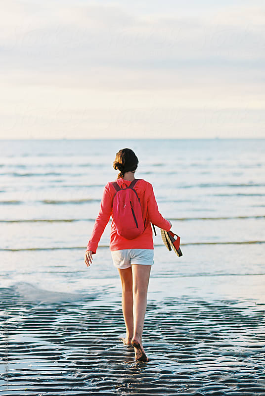 young woman walking on the beach with shoes in her hands by Léa Jones for Stocksy United