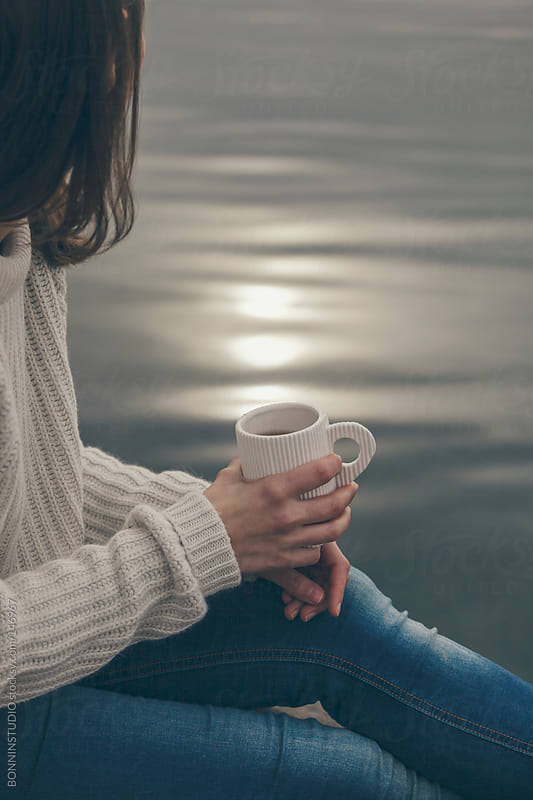 Closeup of woman with cup of tea at the lakeshore. by BONNINSTUDIO for Stocksy United