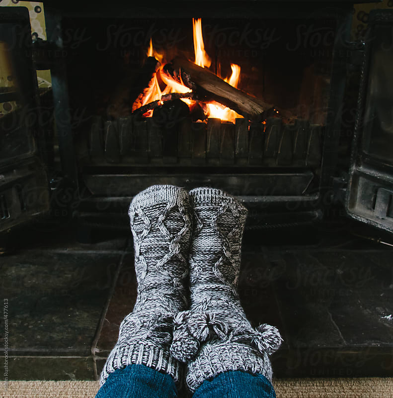 Cosy feet in front of a fire. by Helen Rushbrook for Stocksy United