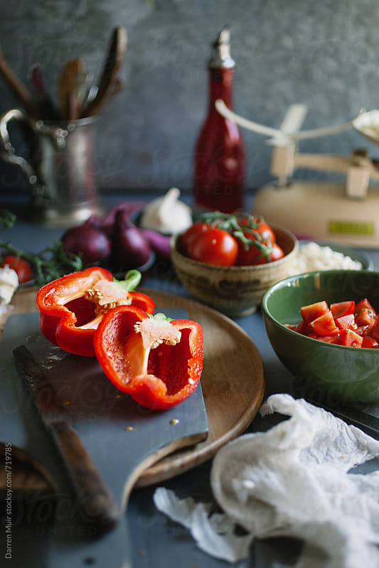 Half red peppers sit on a cutting board surrounded by other ingredients on a table. by Darren Muir for Stocksy United