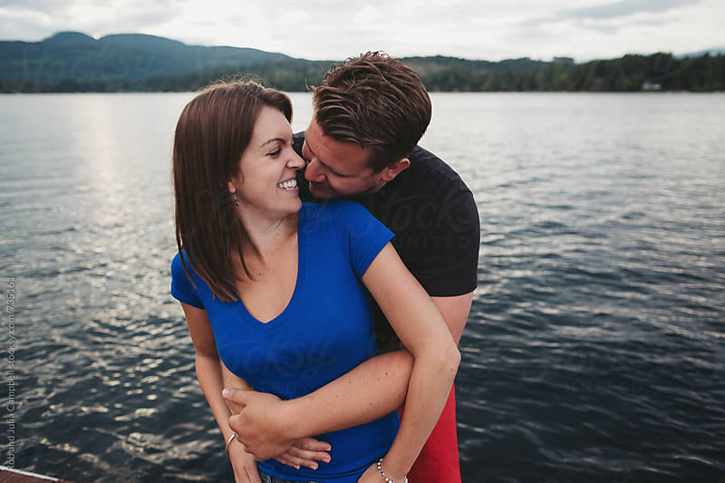 Young playful couple together on dock at lake by Rob and Julia Campbell for Stocksy United
