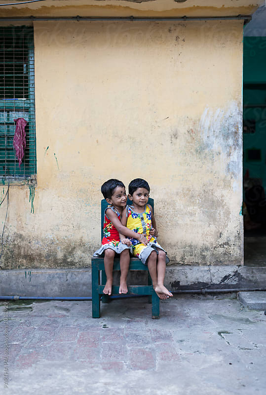 Twin girls sit together in a chair by PARTHA PAL for Stocksy United
