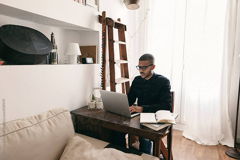 Latin man working with laptop at home office. by BONNINSTUDIO for Stocksy United