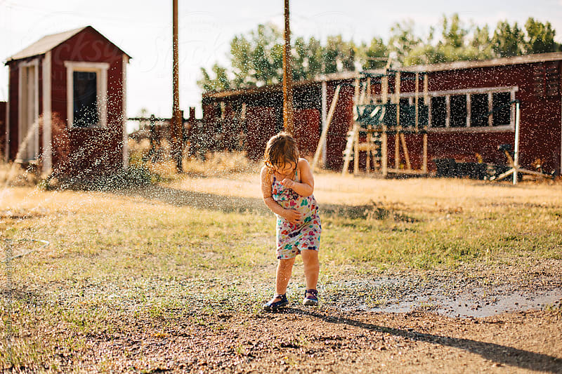 Toddler girl being sprayed by a broken hose while playing outside in the sprinkler. by Jessica Byrum for Stocksy United