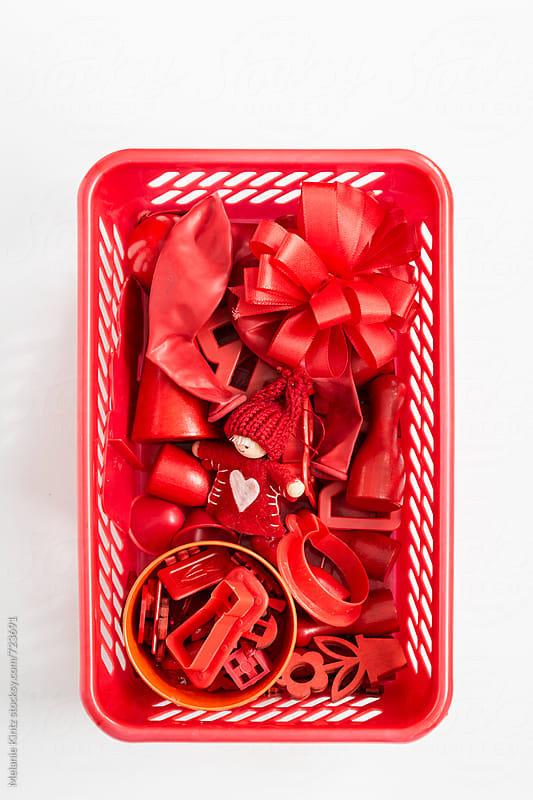 Red toys in red basket on white background by Melanie Kintz for Stocksy United
