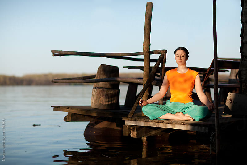 Young woman meditating in nature by the river. by Mosuno for Stocksy United