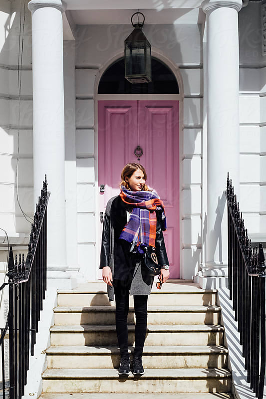 Young Woman Posing in front of the Pink Door by Katarina Radovic for Stocksy United