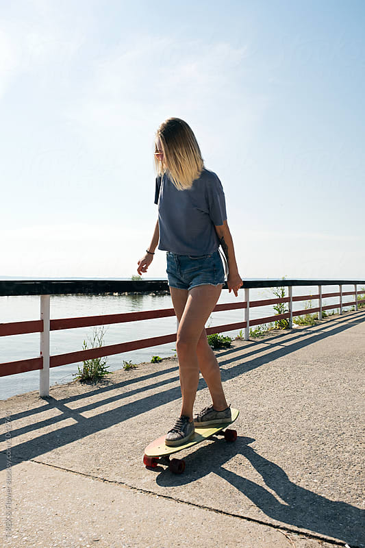 Young girl longboarding on riverside by T-REX & Flower for Stocksy United