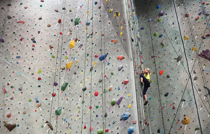 Young girl climbing to the top of a climbing rock wall by Carolyn Lagattuta for Stocksy United