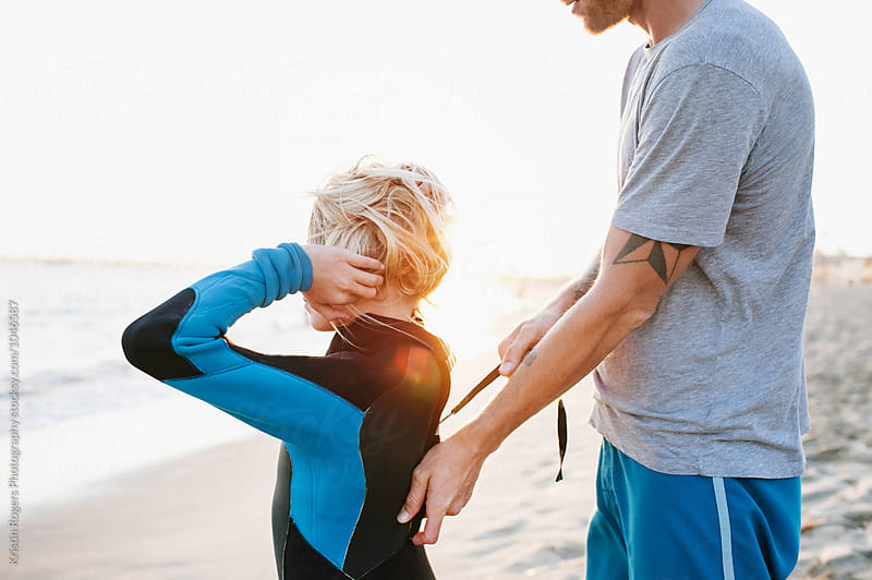 Dad helping daughter zip up wetsuit on beach by Kristin Rogers Photography for Stocksy United