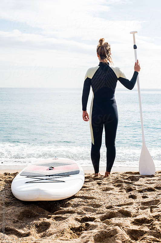 Blonde girl stands up with her paddle looking at the sea  by Bisual Studio for Stocksy United