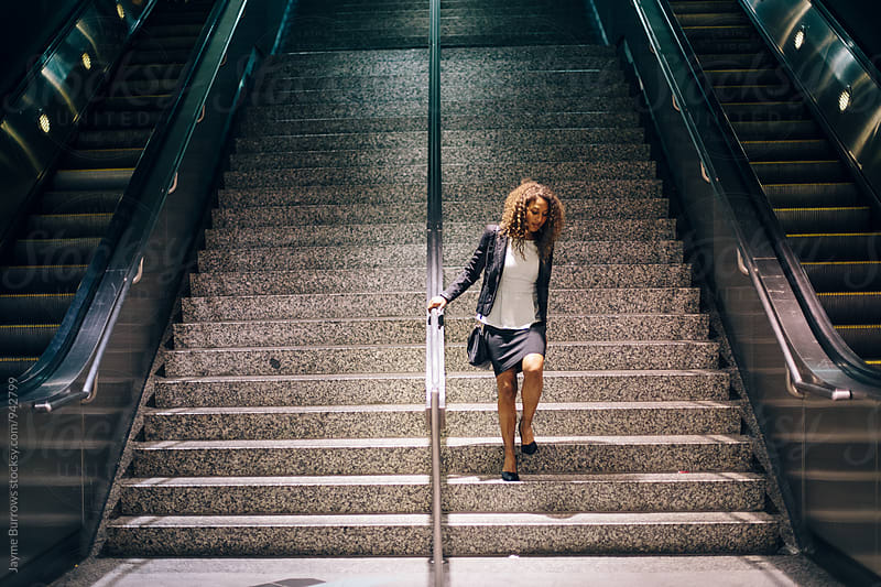 Young, Professional Woman Walkign Down Stairs. by Jayme Burrows for Stocksy United