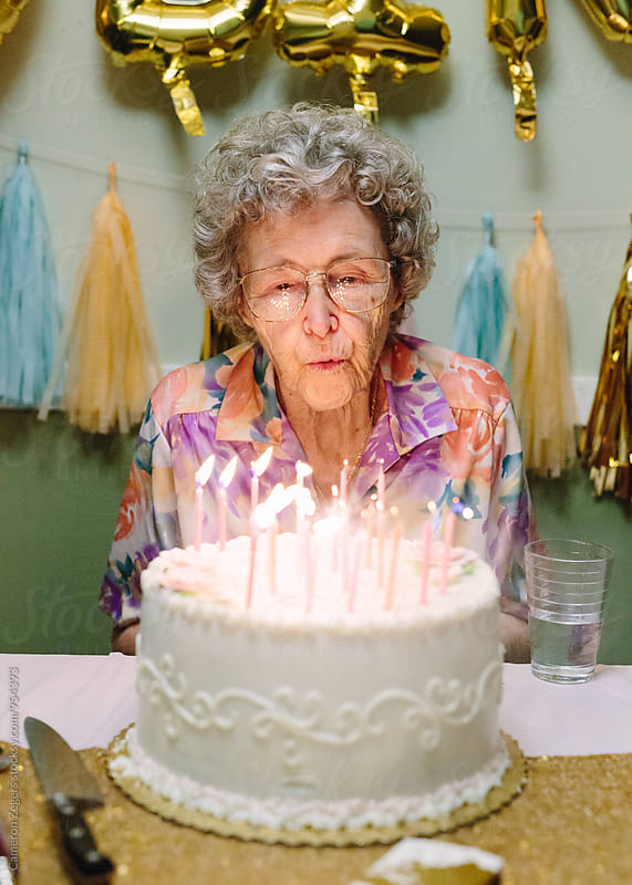 elderly woman blowing out birthday candles on cake by Cameron Zegers for Stocksy United