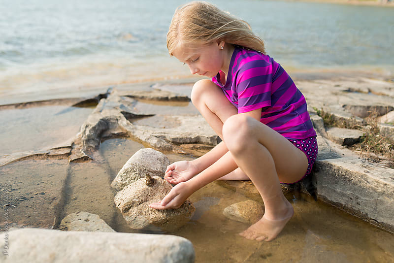 Little Girl Pretending to Kiss Frog on a Rocky Northern Cottage Lakeshore on Warm Sunny Summer Day by JP Danko for Stocksy United