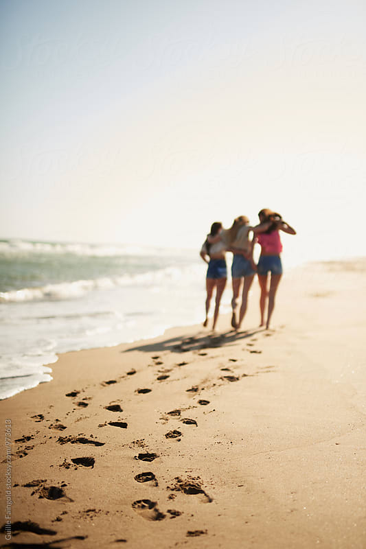 Three unfocused girlfriends walking along the beach by Guille Faingold for Stocksy United