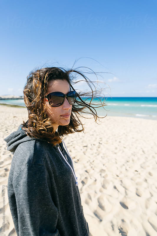 Young woman on a windy day in a beach, wearing sunglasses and a hoodie. by Inuk Studio for Stocksy United