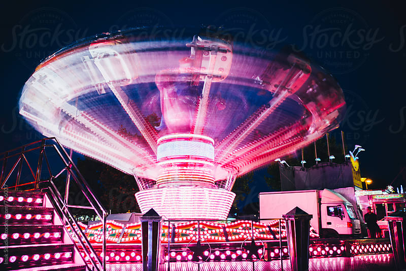 Spinning ride in a fair at night motion blurred in a long exposure shot by Inuk Studio for Stocksy United