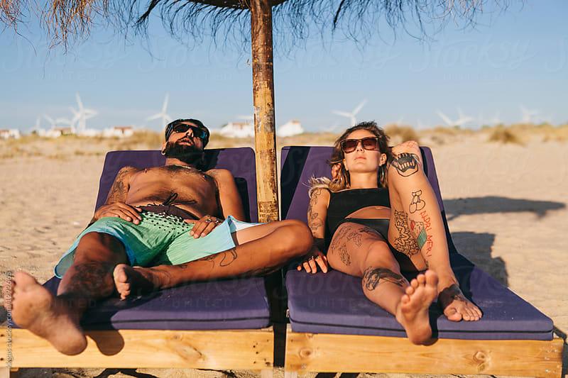Cute tattooed couple sunbathing on loungers on a beach by kkgas for Stocksy United