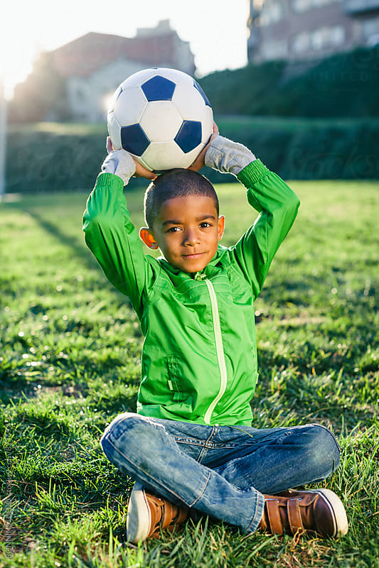 Portrait of a kid holding a soccer ball sitting on grass. by BONNINSTUDIO for Stocksy United