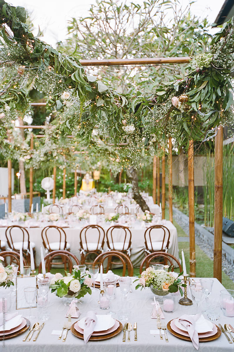Outdoor, tropical wedding reception with hanging greenery garlands by Seth  Mourra - Outdoors, Wedding reception - Stocksy United