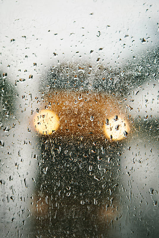 School bus through window on rainy day by Stephen Morris for Stocksy United