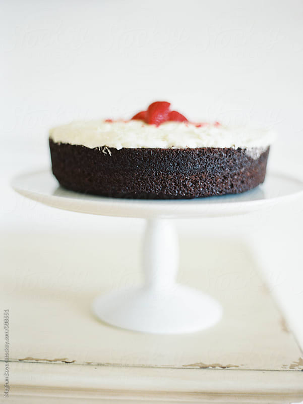 Delicious chocolate cake with white icing on a white stand by Meghan Boyer for Stocksy United