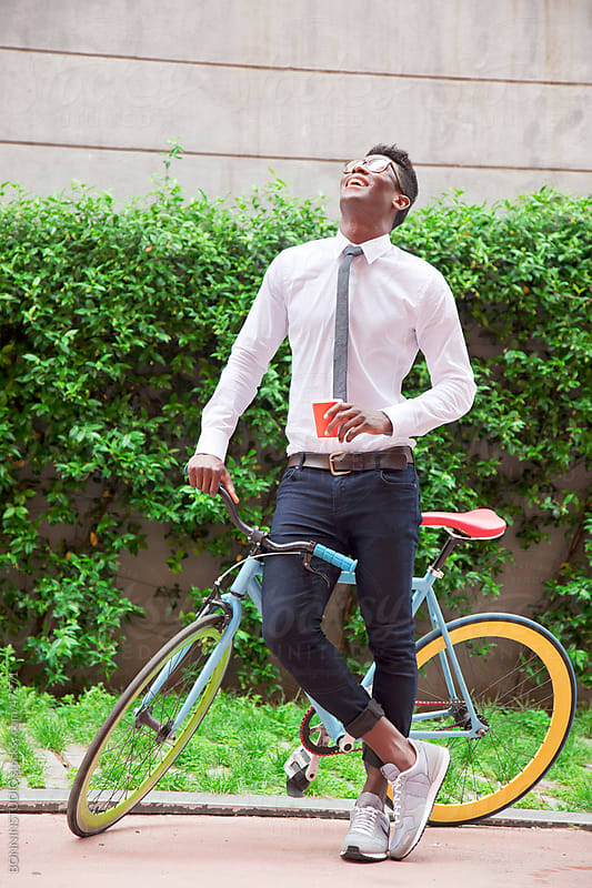 Laughing african young man in the park by BONNINSTUDIO for Stocksy United