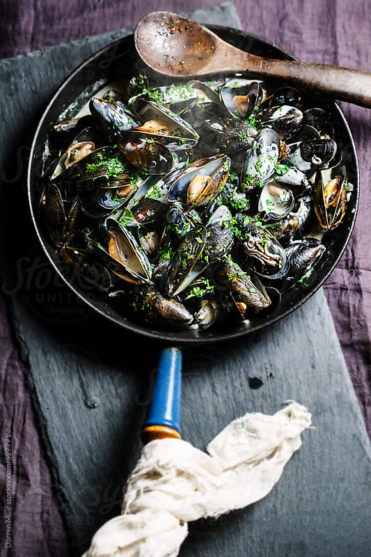 Moules mariniere, cooked in a pan just of the stove. by Darren Muir for Stocksy United